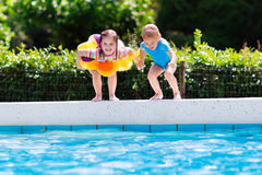 Kids jumping into swimming pool Stock Image