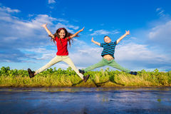 Kids jumping on wet road. Happy kids jumping on wet road after rain Royalty Free Stock Photography