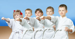 Kids in karategi are hitting punch arm Royalty Free Stock Photography