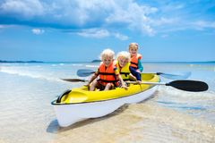 Kids kayaking in ocean. Children in kayak in tropical sea. Active vacation with young kid. Boy and girl in canoe on beautiful beach. Holiday activity with stock photo