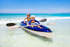 Kids kayaking in ocean. Children in kayak in tropical sea Stock Photos