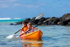 Kids kayaking in ocean Stock Photo
