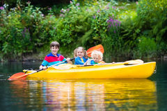 Kids kayaking on a river. Happy family with three kids enjoying kayak ride on beautiful river. Little girl, toddler boy and teenager kayaking on hot summer day royalty free stock image