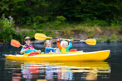 Kids kayaking on a river. Happy family with three kids enjoying kayak ride on beautiful river. Little girl, toddler boy and teenager kayaking on hot summer day stock photos