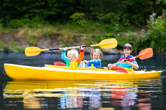 Kids kayaking on a river. Happy family with three kids enjoying kayak ride on beautiful river. Little girl, toddler boy and teenager kayaking on hot summer day royalty free stock photography