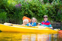 Kids kayaking on a river. Happy family with three kids enjoying kayak ride on beautiful river. Little girl, toddler boy and teenager kayaking on hot summer day royalty free stock photo