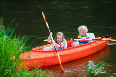Kids kayaking in summer sport camp. Family on kayak and canoe tour. Two little kids paddling in kayaks in a river on a sunny day. Children in summer sport camp royalty free stock photo
