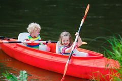 Kids kayaking in summer sport camp. Family on kayak and canoe tour. Two little kids paddling in kayaks in a river on a sunny day. Children in summer sport camp royalty free stock photos