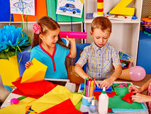 Kids keeps colored paper on table in kindergarten . Stock Images