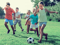 Kids Kicking Football In Park Royalty Free Stock Photography