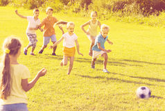 Kids kicking football in park Royalty Free Stock Images