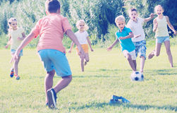 Kids kicking football in park. Active kids 7-11 years old having fun and kicking football in park on summer day Stock Photography