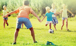 Kids kicking football in park. Cheerful, happy kids having fun and kicking football in park on summer day royalty free stock photography