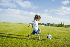 Kids kicking soccer ball Royalty Free Stock Photography