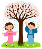 Kids in kimonos standing under a sakura tree. Japanese children in traditional kimonos standing under a blooming cherry tree. The boy is holding dango rice Royalty Free Stock Photo