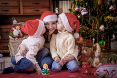 Kids kissing theit mother at cheek under Christmas tree Stock Photo