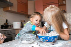 Kids on a kitchen cooking a dinner and have fun. Realy nice couple of exited children's doing a job on a kitchen royalty free stock images