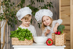 Kids in the kitchen making vegetable salads. Healthy food. Vegetables. Family Stock Images