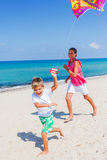 Kids with kite. Summer vacation - Cute boy and girl flying kite beach outdoor Royalty Free Stock Images