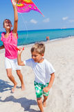 Kids with kite. Summer vacation - Cute boy and girl flying kite beach outdoor Royalty Free Stock Photo