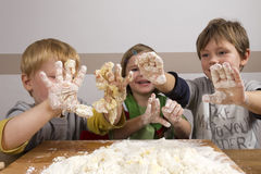 Kids kneading dough Royalty Free Stock Images