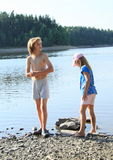 Kids by a lake. Little barefoot girl in blue t-shirt with cherries and boy in grey shorts standing in front of lake Stock Image