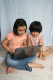 Kids and laptop. Two little girls looking and using the laptop Royalty Free Stock Photography