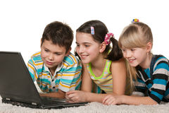 Kids with laptop on the carpet. Three cheerful children with a laptop are lying on the carpet; isolated on the white background Royalty Free Stock Images