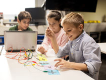 Kids, laptop and invention kit at robotics school. Education, children, technology, science and people concept - group of happy kids with laptop computer playing royalty free stock photography