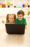 Kids with laptop laying on the floor Royalty Free Stock Images