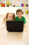 Kids with laptop laying on the floor at home Royalty Free Stock Image
