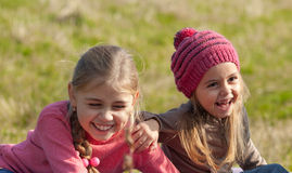 Kids laughing. Two girl on a lawn. Little girl with her older sister laughing Stock Images