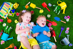 Kids on a lawn with garden tools Royalty Free Stock Images