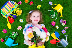 Kids on a lawn with garden tools. Kids gardening. Children with garden tools. Child with watering can and shovel. Little kid watering flowers. Girl relaxing on royalty free stock photo