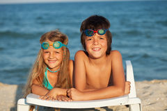 Kids laying on beach chair wearing swimming goggles Royalty Free Stock Photo