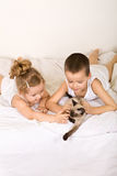Kids laying in bed playing with their kitten Stock Image