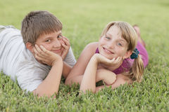 Kids laying on the grass Royalty Free Stock Image