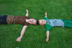 Kids laying on grass Royalty Free Stock Photos