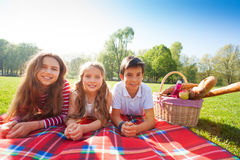 Kids laying on the picnic blanket in summertime. Three happy kids laying on the picnic blanket in a line next to the basket with French baguettes, fruits and Stock Image