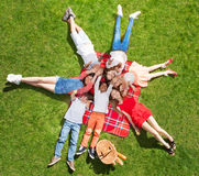 Kids laying on the picnic blanket and waving hands. Top view portrait of seven happy kids laying in a circle on the picnic blanket on green lawn and waving hands Royalty Free Stock Images