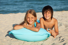 Kids laying in the sand on a beach Stock Image