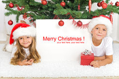 Kids laying under the christmas tree Royalty Free Stock Image
