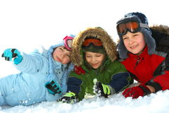 Kids laying in winter snow. A view of three happy, smiling children lying together in the winter snow, all bundled up in warm coats and clothing Stock Photography