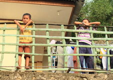 Kids leaning on railings. Barefoot kids - girl and boy leaning on railings of their house in Labuan Bajo (Flores, Indonesia Royalty Free Stock Photography