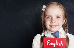 Kids learn english concept. Closeup portrait of cute child girl. With english book on chalkboard in language school royalty free stock photography