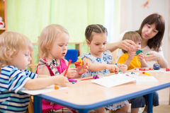 Kids learning arts and crafts in kindergarten with teacher. Kids group learning with teacher arts and crafts in day care centre playroom royalty free stock photography