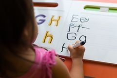 Kids learning how to write the abc`s at home. Kids learning in classroom. homeschooling concept. close of tracing the alphabet stock photos