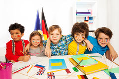 Kids learning languages sitting in line at a desk Stock Photos