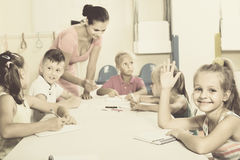Kids learning to write on lesson in elementary school class. Cheerful diligent kids learning to write on lesson in elementary school class Royalty Free Stock Photos