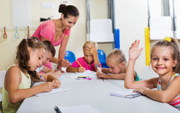 Kids learning to write on lesson in elementary school class Stock Images